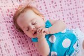 Sweet Little Baby Sleeping. She In Blue Dress With White Polka Dots.