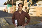 Portrait of a smiling confident supervisor with clipboard outside warehouse against stack of wood