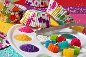 Colorful still life of cupcake supplies with an artist's theme - includes wrappers with splattered p