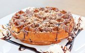 Fresh waffle with chocolate, syrup and grated hazelnut
