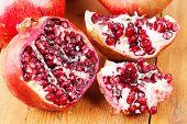 Cut Open Pomegranate On Wooden Cutting Board