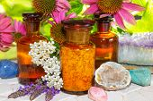 stock photo of naturopathy  - Naturopathy with gemstones for crystal healing and flowers including lavender and echinachea for alternative medicine with essential oil plant extracts and dried plants for aromatherapy - JPG