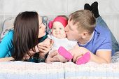 Young Father, Beautiful Mother Kiss Cute Baby And Lie On Bed At Home.