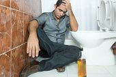 Drunk and depressed man sitting in the toilet floor with a bottle of liquor