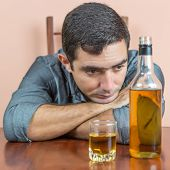 Drunk and depressed hispanic  man with an alcoholic liquor bottle and a glass containing whisky or r