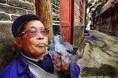 Chinese Peasant Smokes Tube Before Of His House. Age Of Chinese Man Smoked Pipe And Releases Tobacco