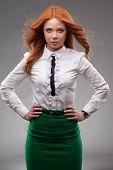 red-haired businesswoman portrait over gray