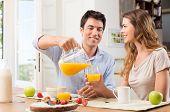 Retrato de hombre feliz verter jugo en vaso para la mujer joven