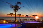 Horario de verano: Hermoso amanecer en zona de piscina con palmeras y sombrillas, Tropea, Italia