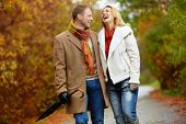 Portrait of ecstatic couple during walk in autumnal park