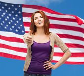 gesture and happy people concept - smiling girl in casual clothes showing thumbs up over american fl