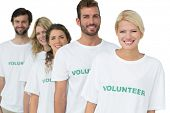 Group portrait of happy volunteers standing in a row over white background