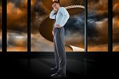 Thinking businessman with hand on head against winding staircase in orange sky
