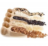 Wooden scoops with different rice types scattered isolated on white background