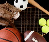High angle view of a group of assorted sporting gear. Items include, Baseball, basketball, soccer ball, football, tennis racket, glove and bat over a black background.