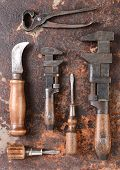 High angle shot of a group of antique hand tools on a rusty metal surface. tools include: pipe wrench, screw drivers, knife, pliers,