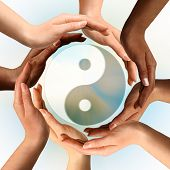 Conceptual yin-yang symbol with multiracial hands surrounding it. Balance, peace, meditation, spirit