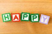 Toy block with spelt in happy