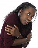 Close-up of an attractive tween girl scrunched up shivering.  Motion blur on closest hand.  On a white background.