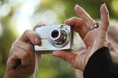 Senior female hands holding compact point-n-shoot photo camera, shooting outdoors. Closeup, shallow DOF