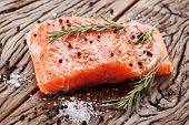 Salmon filet with spices on a wooden carving board. Macro shot.