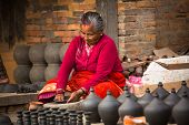 BHAKTAOUR, NEPAL - DEC 7: Unidentified Nepalese woman working in the his pottery workshop, Dec 7, 20