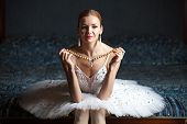 Ballerina holding pearl necklace