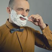 Hipster. Funny portrait of trendy man making moustache and beard of shaving foam and gives wink, ton