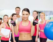 fitness, sport, training and lifestyle concept - personal trainer with group of smiling people in gy
