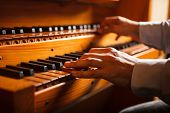 stock photo of church  - Detail of a man playing a church organ - JPG