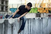 Young Man Sitting And Balancing On Wall, Looking Down