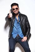 happy man in leather jacket and sunglasses making the ok thumbs up hand sign