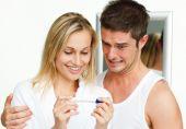 Постер, плакат: Счастливая женщина и испуганный человек изучения тест на беременность