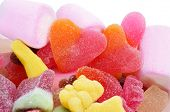 closeup of a pile of different candies, with a pair of heart-shaped candies in the center