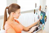 lifestyle, social networking and internet concept - woman using laptop at home