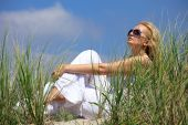 Beautiful Blonde Girl Sitting On A Sand In Dunes