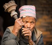 BHAKTAPUR, NEPAL - DEC 7:  Portrait of unidentified Nepalese man smokes on the street, Dec 7, 2013 in Bhaktapur, Nepal. 100 cultural groups have created an image Bhaktapur as Capital of Nepal Arts.