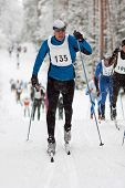 picture of nordic skiing  - Sportsman in classic style cross country skiing race competitors following - JPG