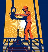 Oil well worker hoisting hook on platform