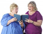 Two senior women singing from the same book.  One looks at the music happily while the other scowls as she looks at her.  On a white background.