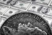 Coin of Silver American Money with words In God We Trust over hundred dollar bills