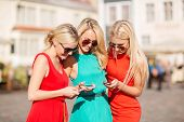 holidays and tourism, modern technology concept - beautiful blonde girls with smartphones in the cit