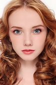 Close-up portrait of young beautiful redhead girl with curly hair