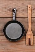Closeup of a cast iron frying pan and a wooden fork hanging on the wall of a rustic kitchen.