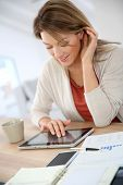 Woman working from home on digital tablet