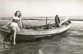 HERINGSDORF, GERMANY, CIRCA 1956 - Vintage photo of young woman on boat