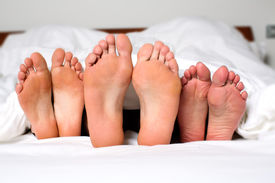 stock photo of swingers  - Humorous image of the bare feet of a man and two women in bed sticking out from under the bedclothes conceptual of a threesome orgy swingers or sexual cheating  - JPG