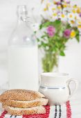 stock photo of milk-pint  - Fresh milk in old fashioned bottle and homemade bread on the napkin - JPG