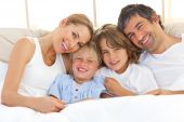 image of happy family  - Happy family reading a book lying in bed - JPG