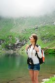 Young caucasian female hiker holding binoculars. A lake surrounded by mountain ridges